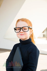 Girl wearing oversized glasses holding laptop
