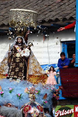 A person throws confetti over statue of Virgen del Carmen during main procession around village , Paucartambo , Peru