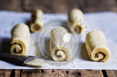 Raw cinnamon buns on wooden table before baking