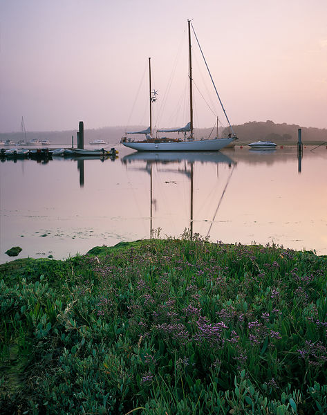 A ketch is moored between the piles at Buckler's Hard on the mirror-like Beaulieu river. The soft lilac in the sky light bath...