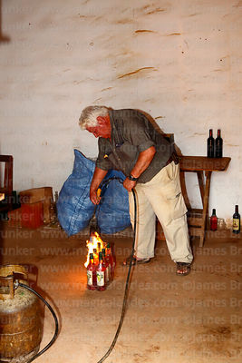 Don Tomas sealing a pack of bottles of ratafia with a homemade gas blow torch in his bodega, Villa Abecia, Chuquisaca Departm...