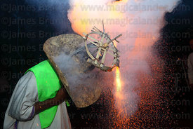Close up of fireworks spinning and exploding on a mans hat, San Ignacio de Moxos, Bolivia
