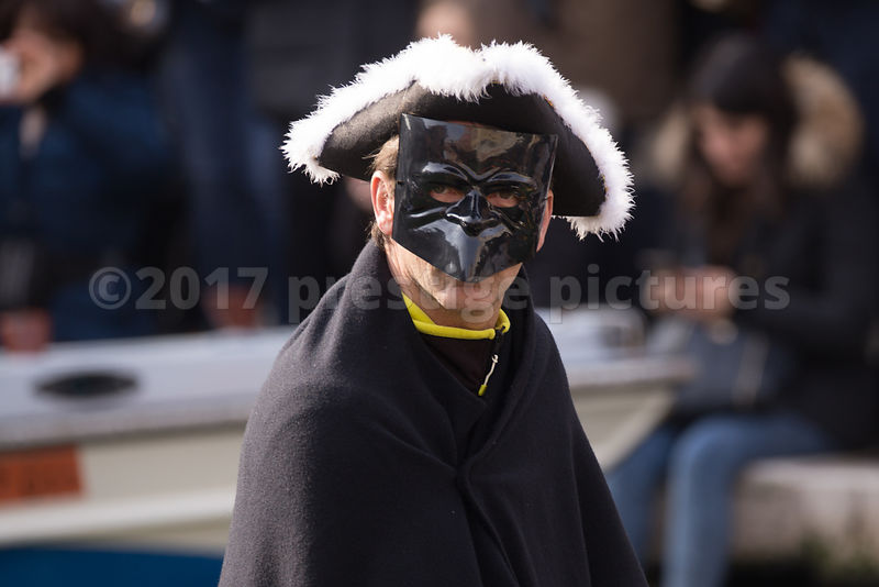 Man in black Bauta Mask and fur lined tricorn hat in the Venice Carnival Water Parade