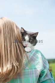 Cute cat looking over little girl's shoulder