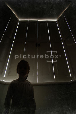 The silhouette of a little girl in front of closed window shutters, with daylight coming through.