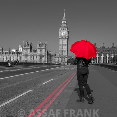 Tourist with red umbrella on Westminster Bridge, London, UK