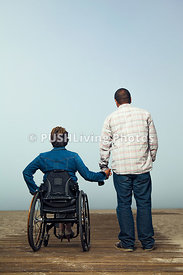 A woman in a wheelchair hand in hand with her boyfriend on a coastal boardwalk