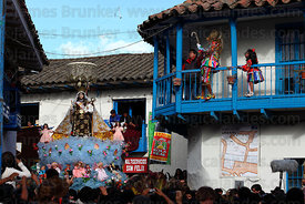 Saqra dancers / devils on balcony taunt the Virgen del Carmen during main procession around the village , Paucartambo , Peru