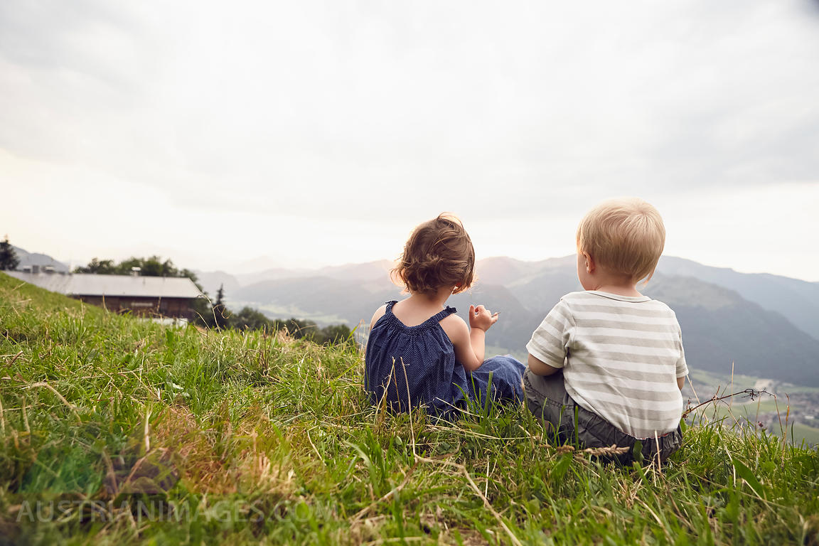 Austria, Tyrol, back view of little girl and boy sitting on Alpine meadow looking at view