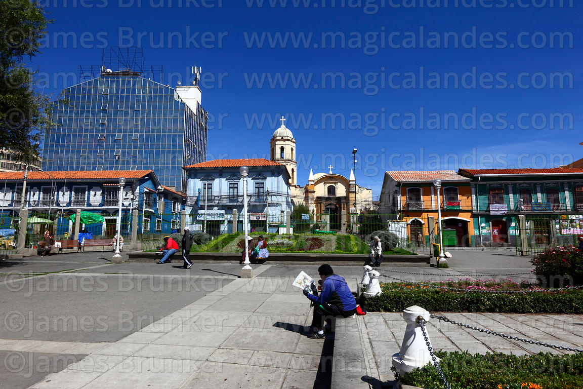 Man reading newspaper in Plaza  Alonso de Mendoza, San Sebastian church in background, La Paz, Bolivia