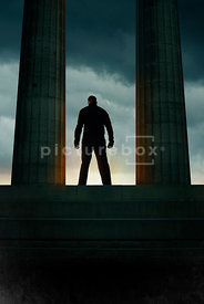 An atmospheric image of a mystery man standing looking out of an old temple.