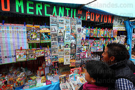 People reading miniature newspapers and magazines on stall, Alasitas festival, La Paz, Bolivia