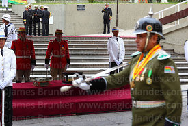 A military police officer wearing an old German style pickelhaube spiked helmet parades past the remains of Eduardo Abaroa, P...