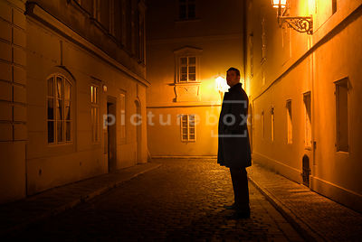 An atmospheric image of a mystery man, in a black coat, standing in an old cobbled street, lit by streetlights, in Prague.