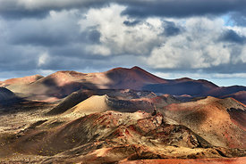 Ancient volcanoes in Timanfaya national park under a cloudy sky