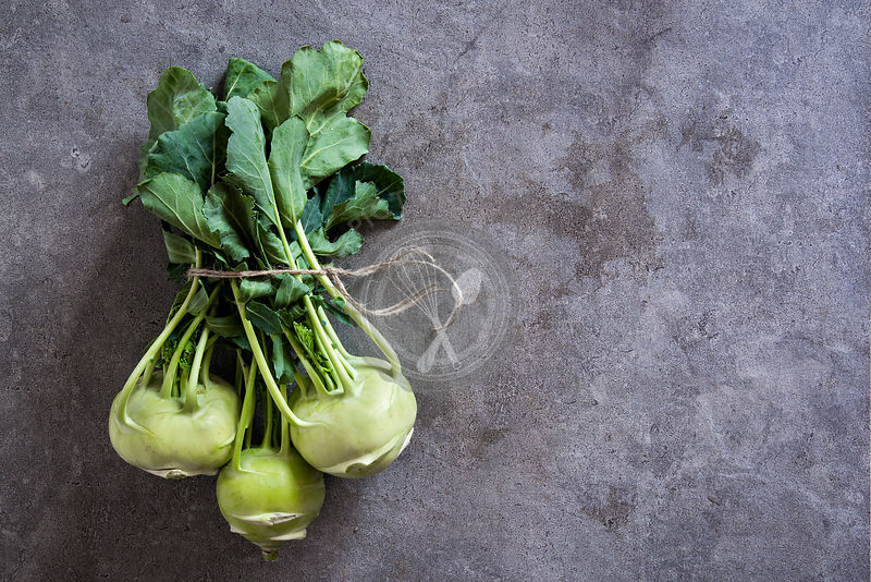 Bundle of fresh kohlrabi stems with leafs over grey concrete background