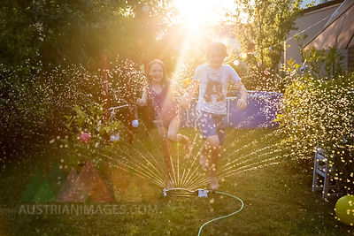 Brother and sister having fun with lawn sprinkler in the garden
