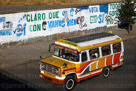 Local public bus called a micro driving past slogans on wall showing support for Evo Morales, El Alto, Bolivia