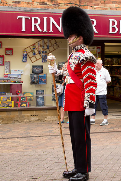 Drum Major from the Coldstream Guards standing to attention outside Trinder Bros Toy Store