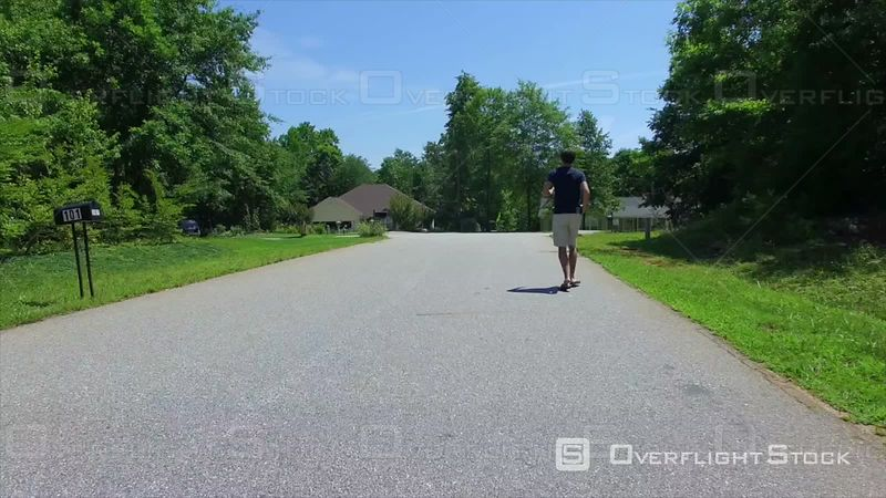 Aerial of Teen Boy Jogging Down Neighborhood Street