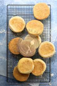Freshly baked English muffins piled on a wire cooling rack.