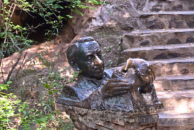 A sculpture of Dr Robert Bloom with a fossil humanoid skull at the entrance to the cave where it was found.