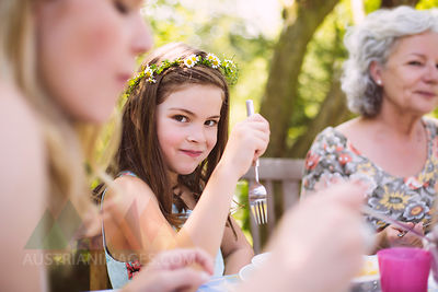 Grl sitting between mother and grandmother at a garden table