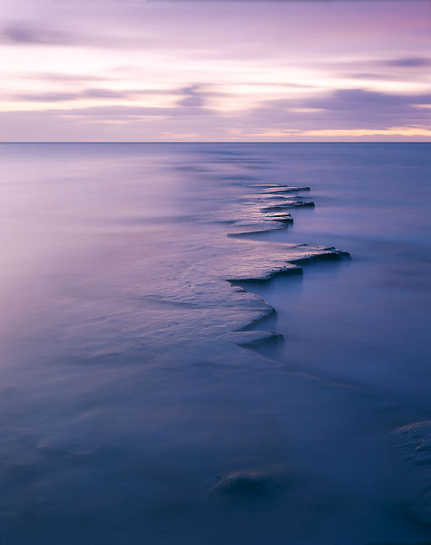 Evening twilight scene on Dorset Jurassic Heritage Coast. Long exposure makes the water appear misty. Cloud formation in dist...