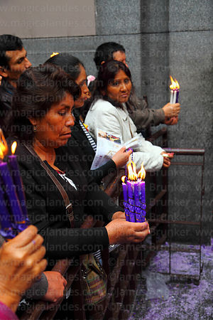 Devotees holding candles praying to Señor de los Milagros in courtyard behind Las Nazarenas church, Lima, Peru