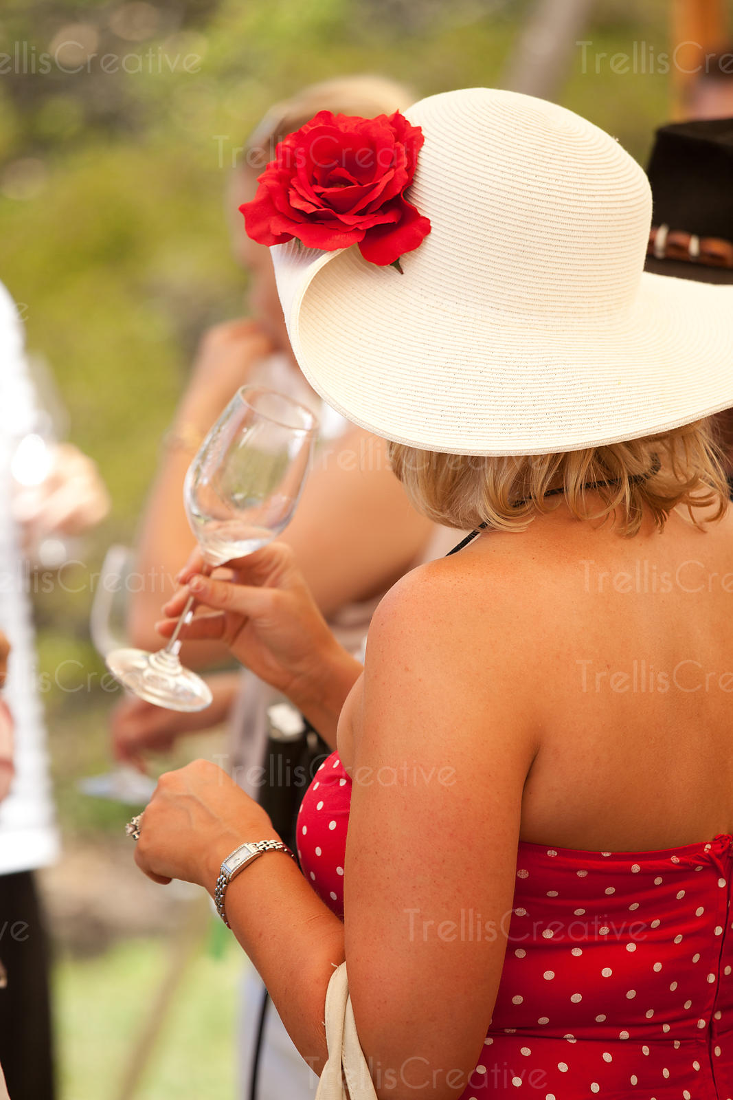 Woman in red dress with white hat drinking wine