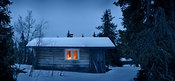 Forest hut lit by candles by winter night