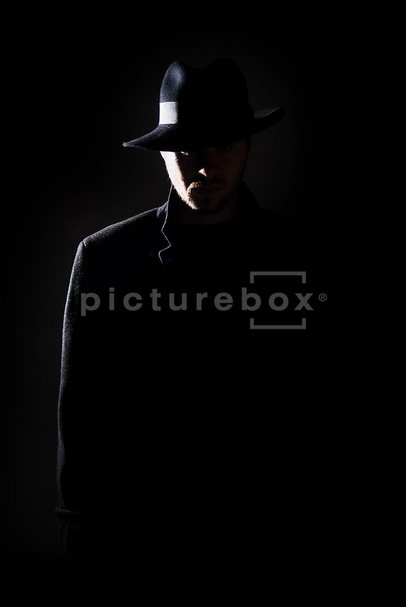 An atmospheric image of a mystery man in a black coat and Fedora hat, standing in the shadows.
