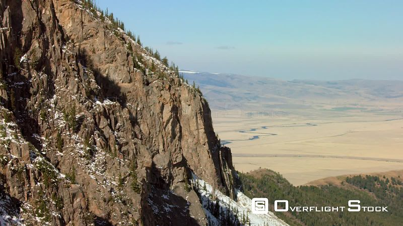 Steep cliffs in the Madison mountain range overlook the Madison valley and Madison river in southwestern Montana
