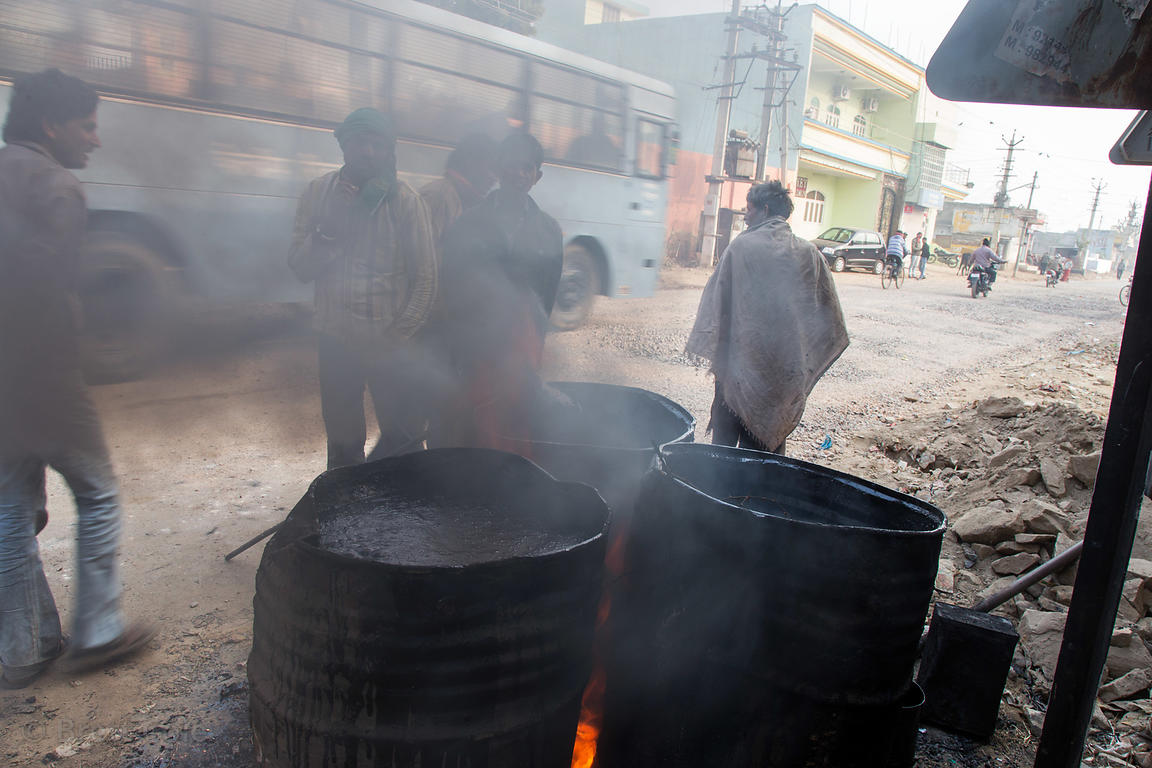 Drums of oil burning and giving off thick black smoke, Rawat Nagar, Ajmer, Rajasthan, India. Air pollution is a major health ...
