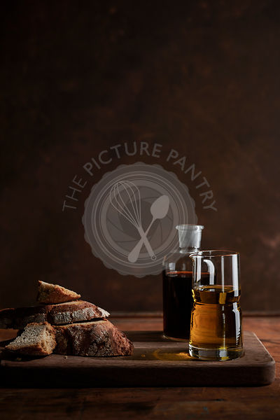 Chunks of rustic, rye bread on a rich wood surface with antique bottles of oil and vinegar.