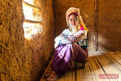 Woman of Padaung (long neck) ethnicity in mud house, Thailand