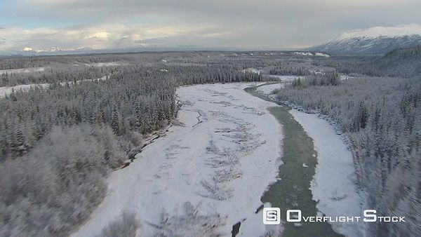 Flying above icy river through scattered forest in Alaska
