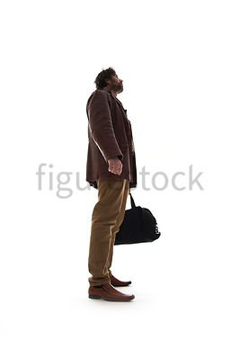 A Figurestock image of a man in a leather Jacket, standing, holding a black bag and looking up – shot from low level.