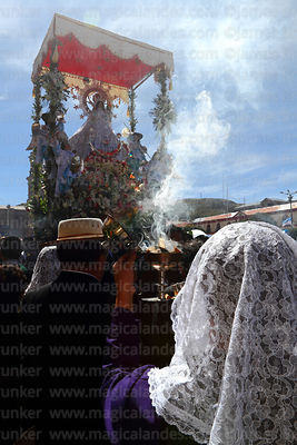 Devotee of Señor de los Milagros holding incense burner in front of Virgen de la Candelaria during main procession, Puno, Peru