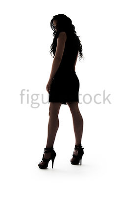 A Figurestock image of a woman, in silhouette, standing, looking over her Shoulder – Shot from Low Level.