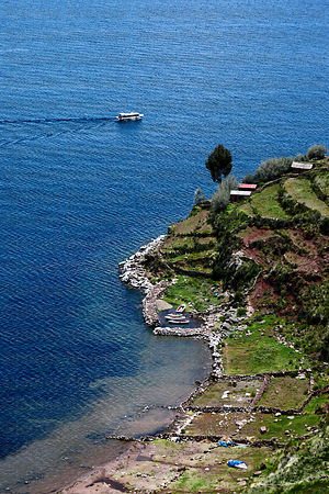 Tourist boat passing harbour and agricultural terraces , Taquile Island , Lake Titicaca , Peru