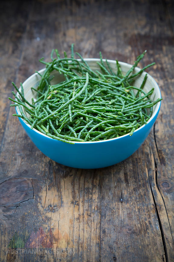 Blue bowl of saltwort, Salicornia, on dark wood