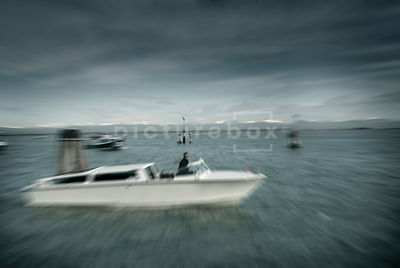 An atmospheric image of a mystery man in a speed boat in Venice, Italy.