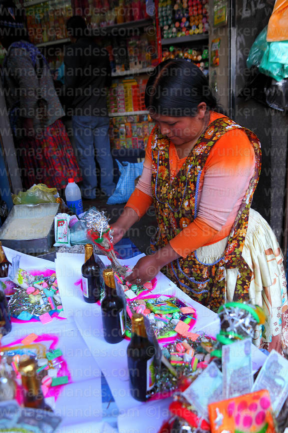 Woman preparing mesa / offerings (called a k'oa) for Pachamama outside her shop in Witches Market, La Paz, Bolivia