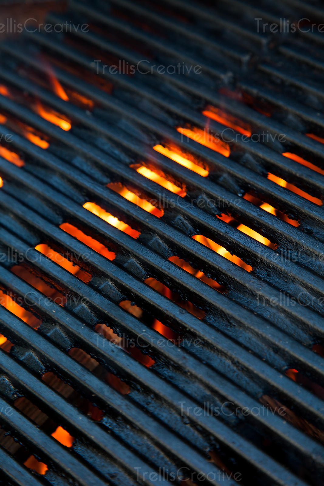 Close-up of hot coals illuminated beneath the grill