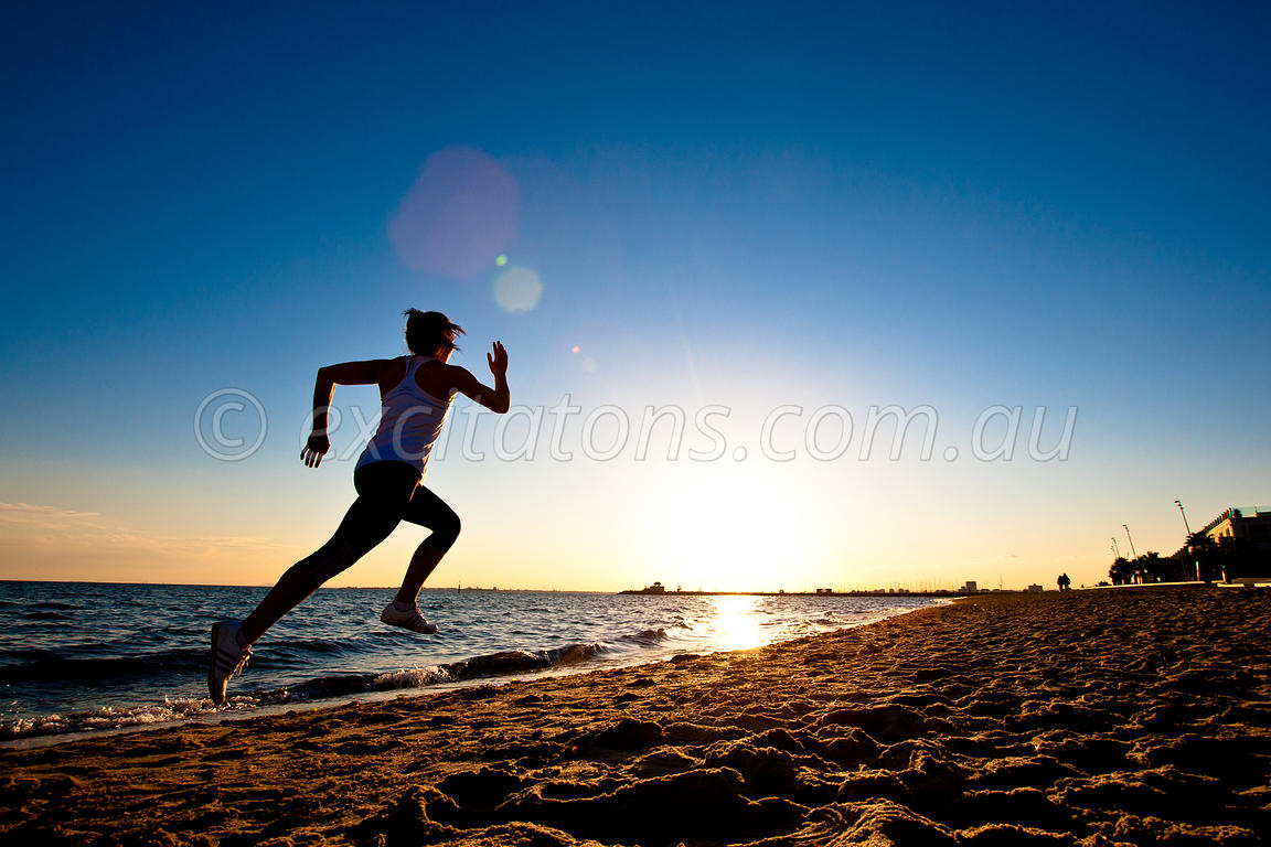 Young athlete running along beach at St Kilda.
