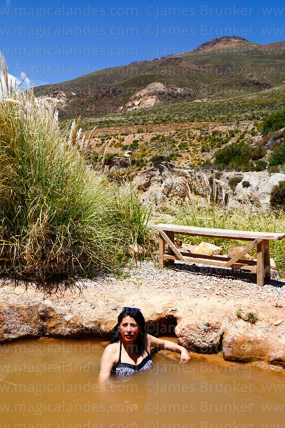 Hispanic girl relaxing in Termas de Jurasi hot springs near Putre, Region XV, Chile