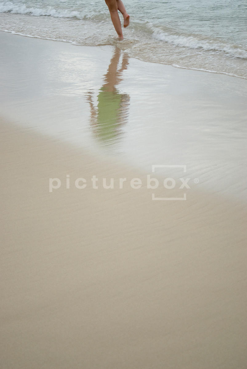 An atmospheric image of the reflection of a girl's running on the beach.