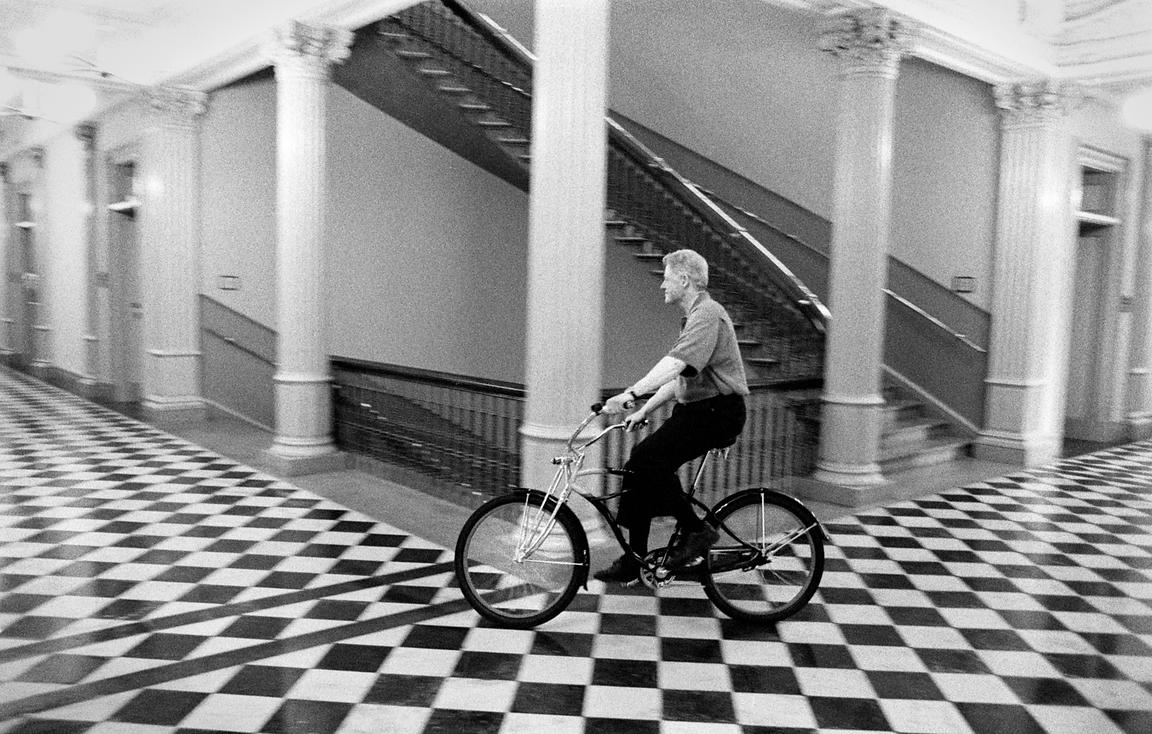 "President William Clinton pokes fun at having more ""free time"" as he rides a bicycle through the Eisenhower Executive Office Building, while making a video for the White House Correspondents video."