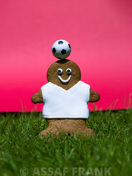 Gingerbread footballer with football on grass